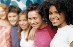 photo of five teenagers in a line hugging and smiling